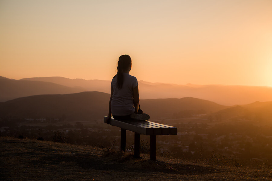 self care, woman sat on hill top