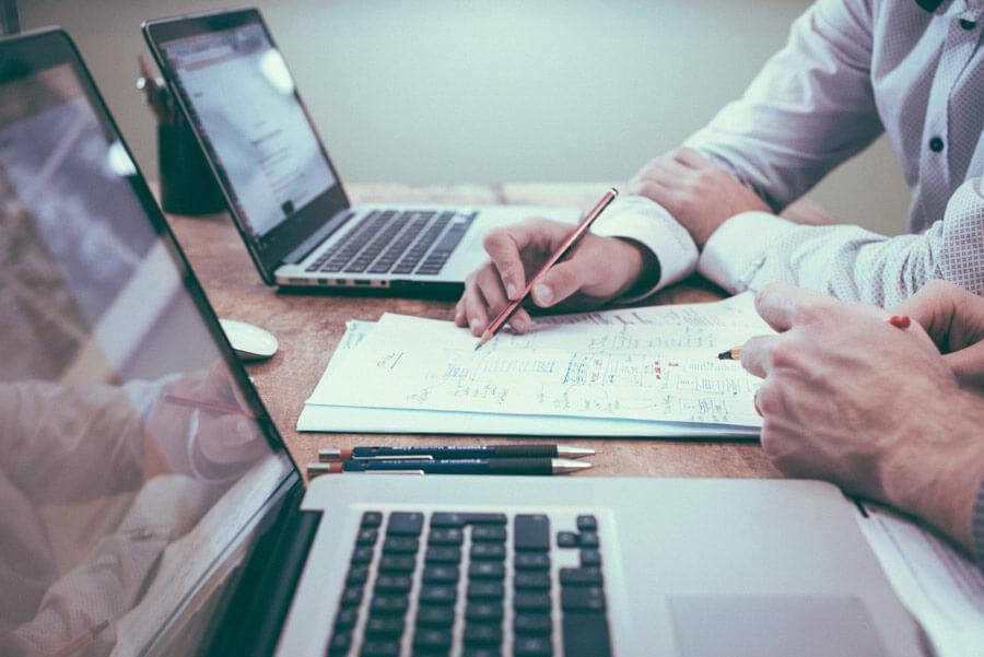 men sat with laptop open, pet business insurance