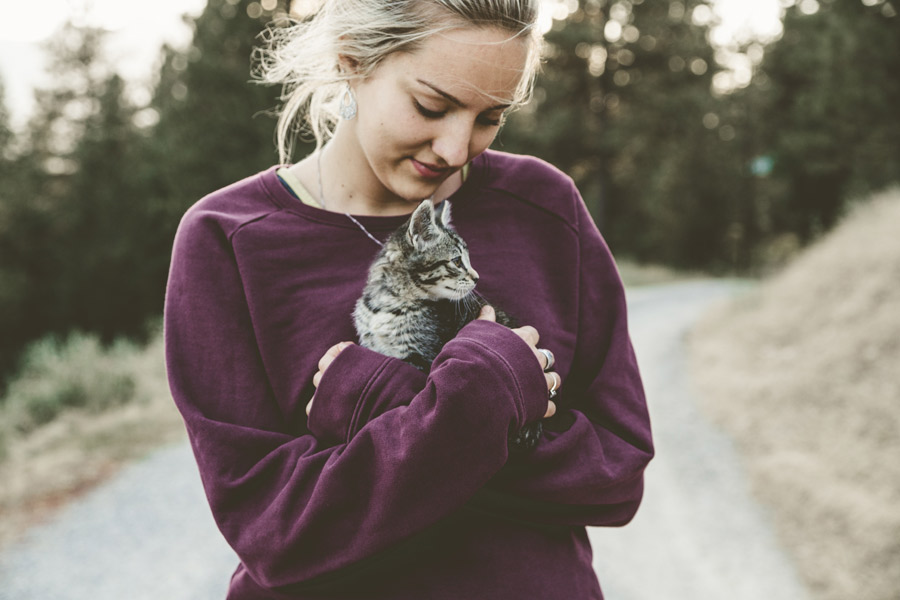 young woman holding cat outdoors