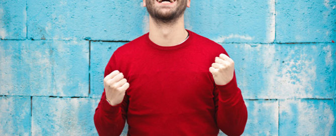 happy man wearing red jumper, managing difficult clients