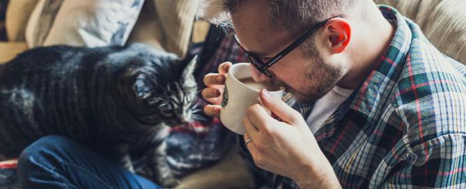 man sat on sofa with cat, pet sitting